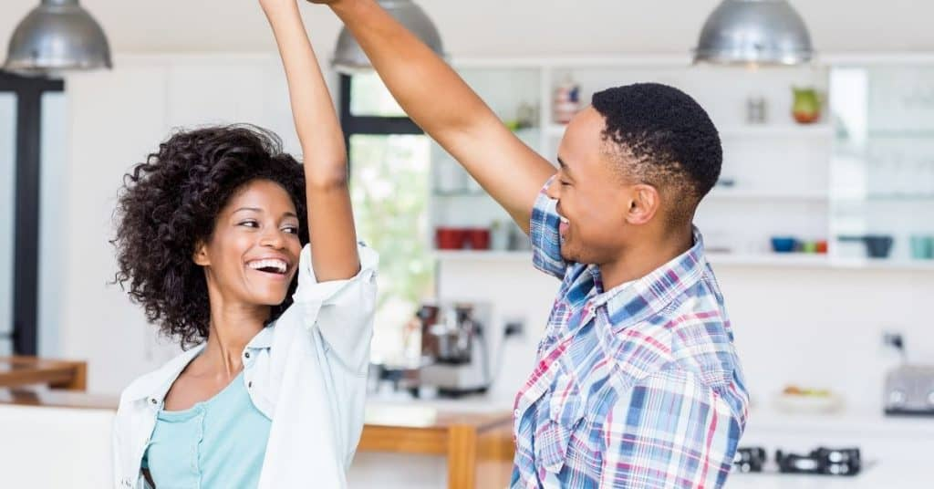 Couple high fiving in the kitchen after doing their housework together.