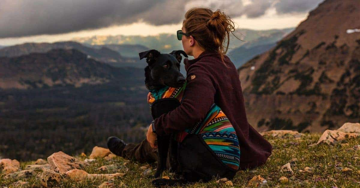 Woman sitting at the edge of the mountain with her dog.