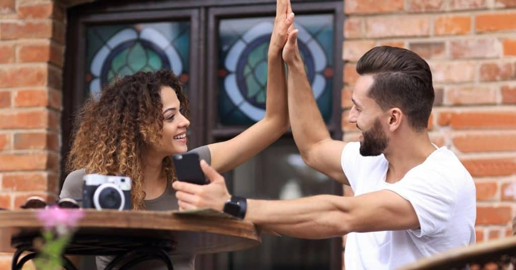 A couple high fiving outside a cafe.