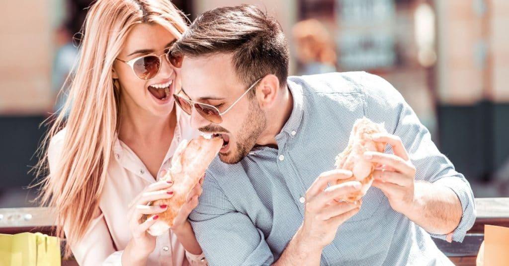 Woman offering her husband her sandwich.