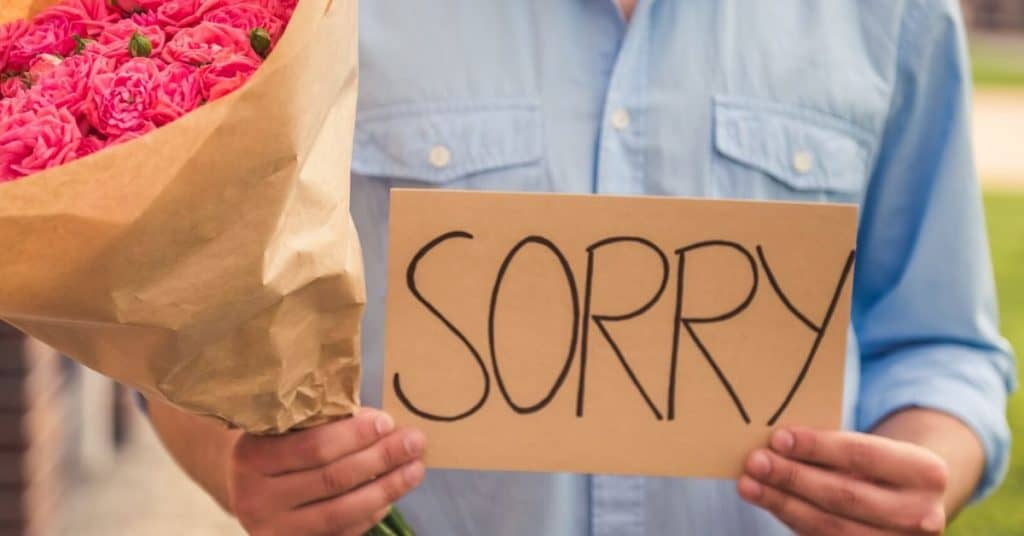 A man holding a bunch of flowers and a sign saying sorry.