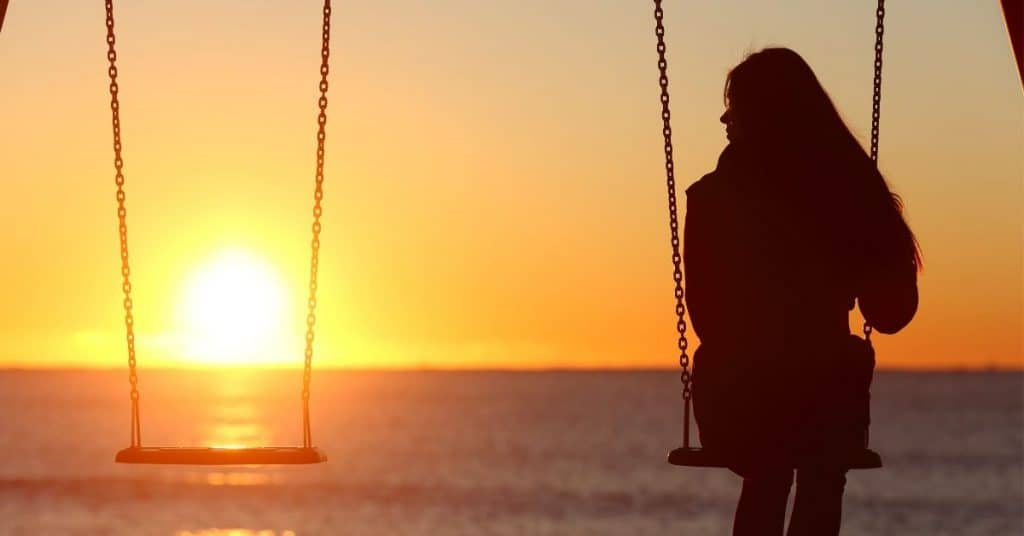 Woman on a swing at sunset. The swing next to her is empty symbolizing that she has lost her husband.