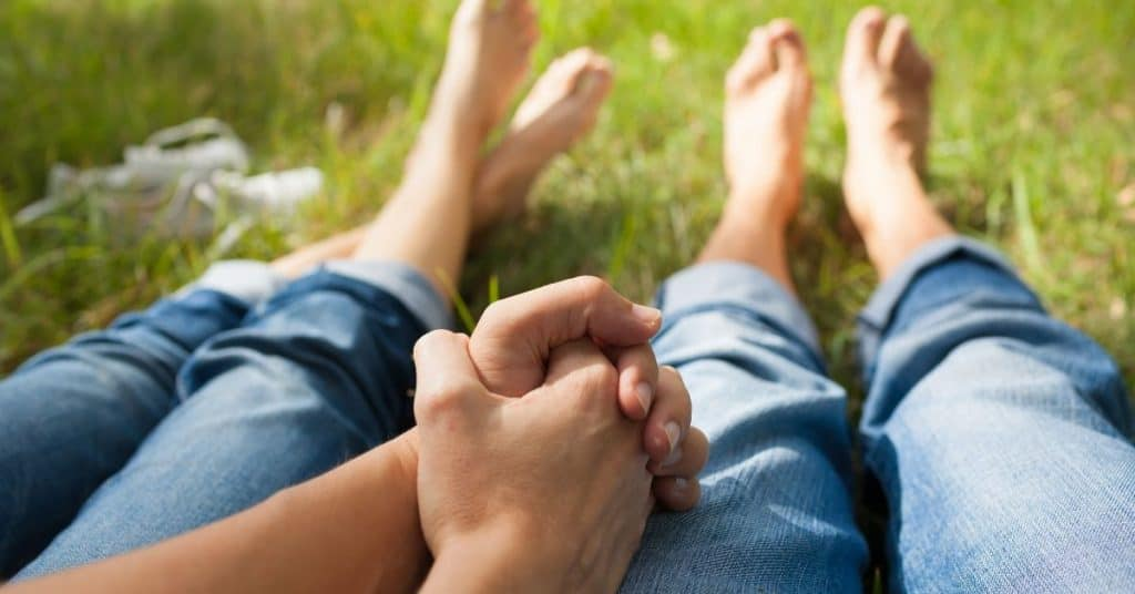 A couple sitting outside in summer holding hands: an example of the physical touch love language