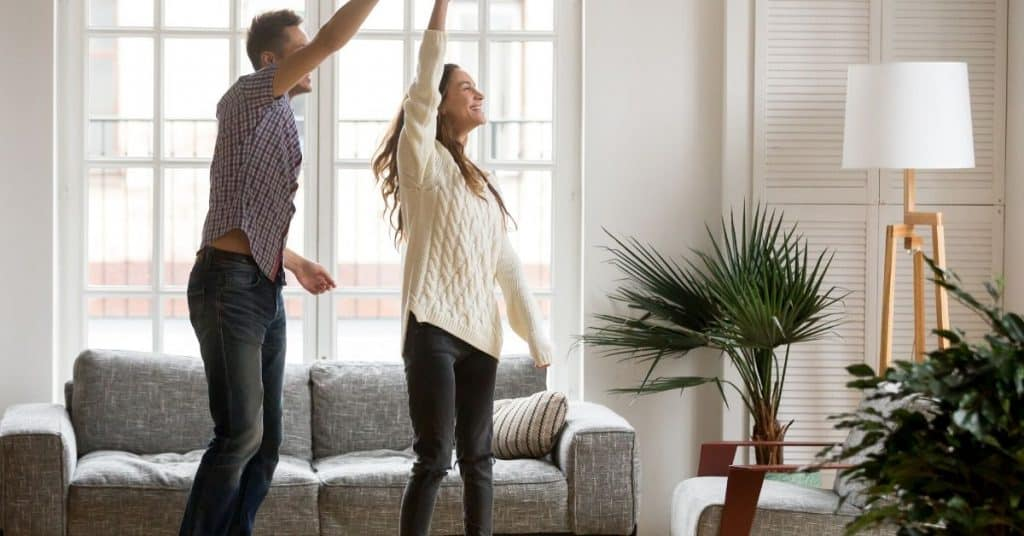 Couple dancing together at home: one of the at home physical touch love language ideas for him.