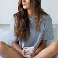 Tired looking woman holding a cup of coffee in bed.