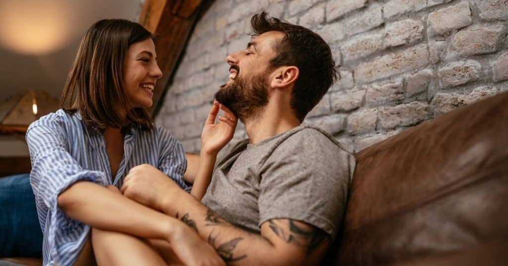 A wife and husband talking on the couch as a way to connect. She is touching his face.
