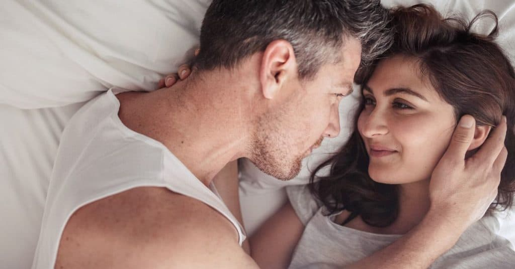 A couple having morning cuddles as a way to connect with your spouse.