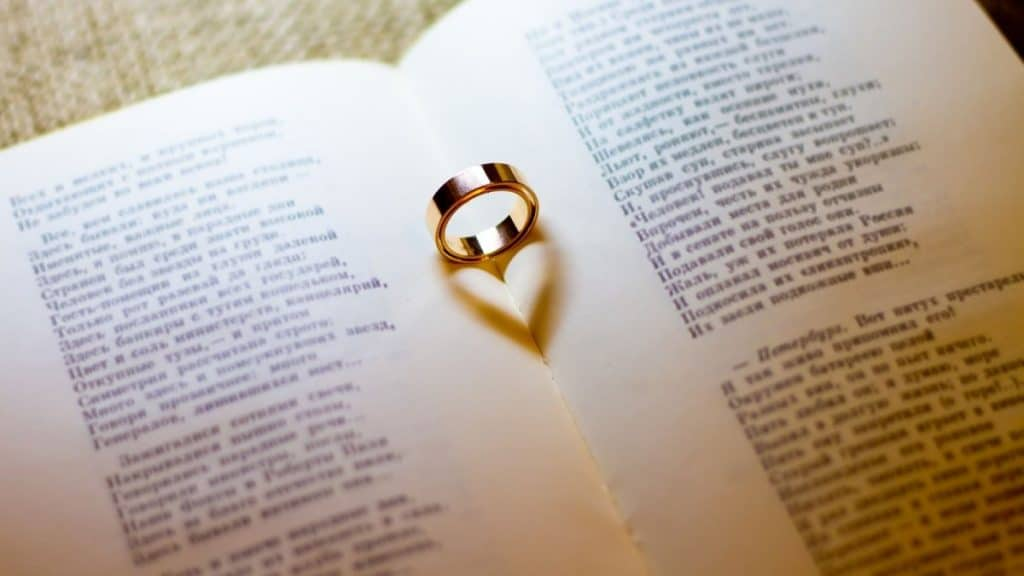 A wedding ring showing a shadow of a heart on a book of readings from a couple's wedding: they are about to reneact their ceremony as a romantic anniversary idea.