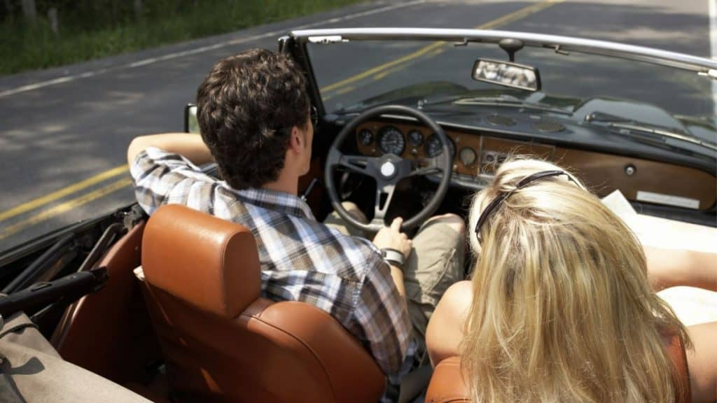 Couple driving in a convertible about to go on a mystery trip as their anniversary celebration.