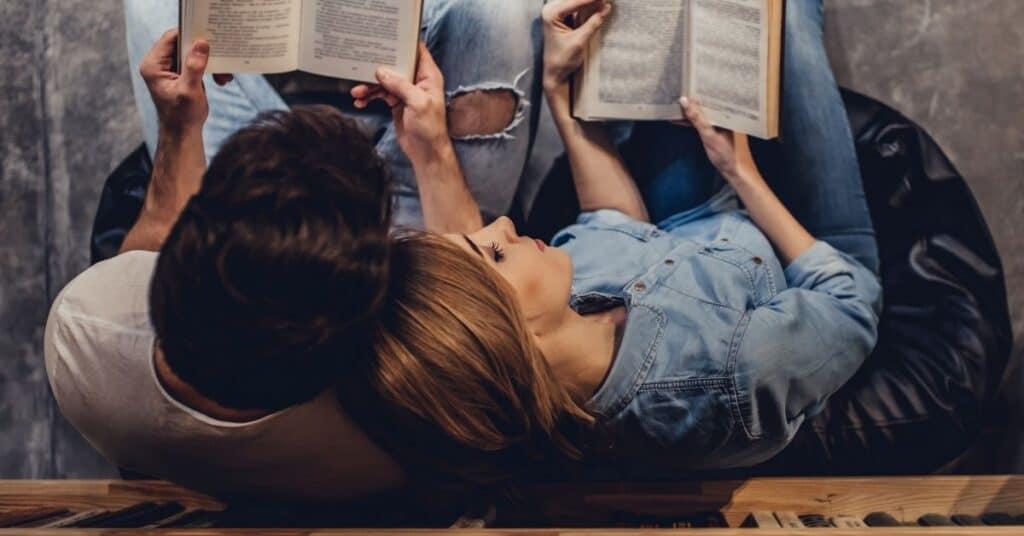 Couple leaning back against bookshelves at the library reading books.