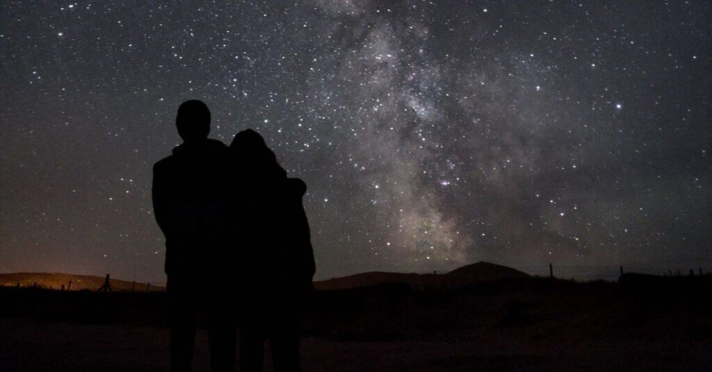 Backs of couple against the star filled sky