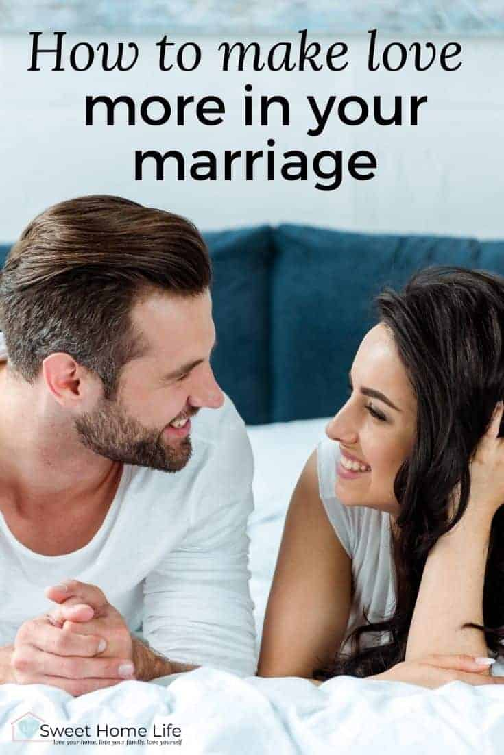 Couple lying in bed smiling at each other with the text overlay, How to make love more in your marriage.
