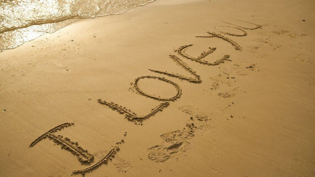 I love you written in the sand at the beach - one of the cute ways to say I love you.