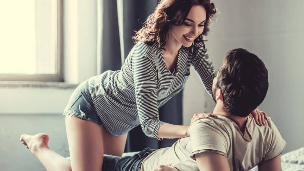A woman in a t shirt and shorts crawling on to her husband lying on the bed.