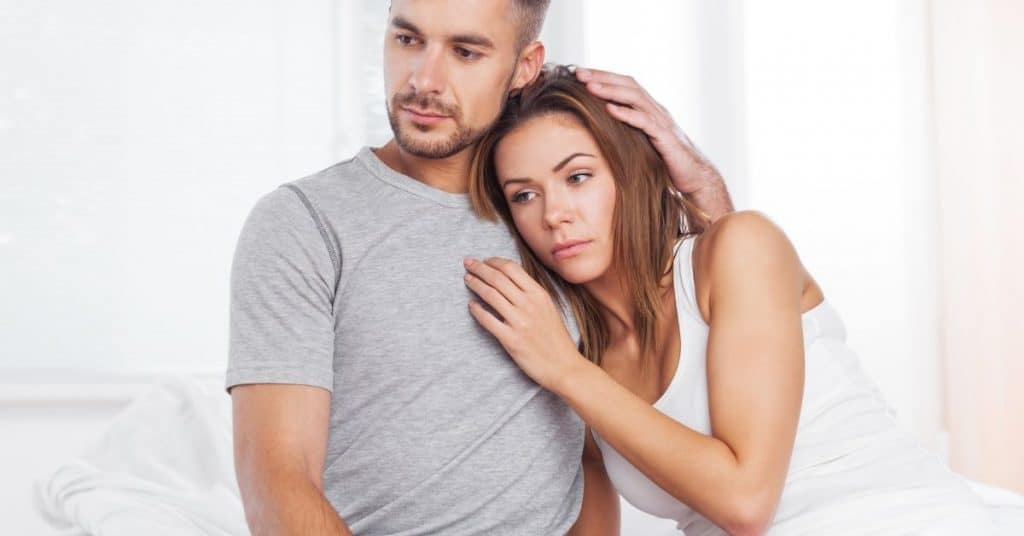 Sad looking couple thinking about couples therapy. They still love each other because they are holding each other but they need some marriage counseling tips.