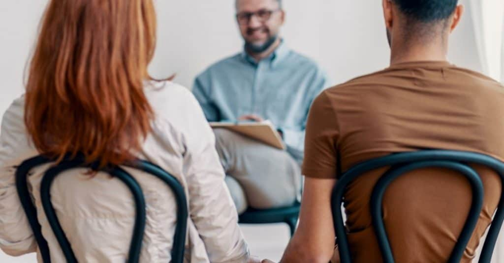 The backs of a couple as they face a marriage counselor: marriage counseling tips