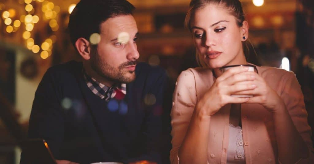 Sad looking couple at a cafe after a marriage counseling session - they need marriage counseling tips.