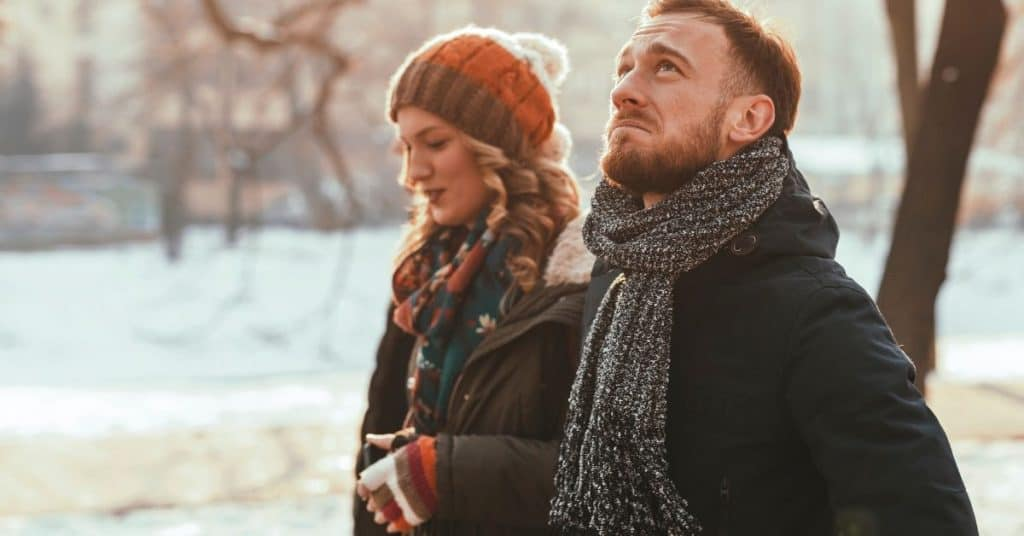 pensive looking couple walking together outside as part of their marriage therapy tips