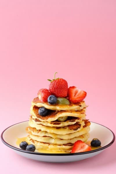A stack of pancakes with fruit on top and a pretty pink background.