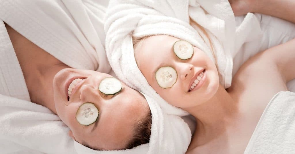 Mother and teenage daughter at a spa together with cucumbers over their eyes