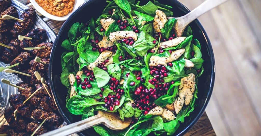 A bowl of green salad with pomegranate seed cooked on a mother son date night.