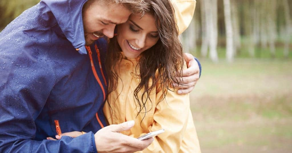 Couple having a rainy day date going geocaching