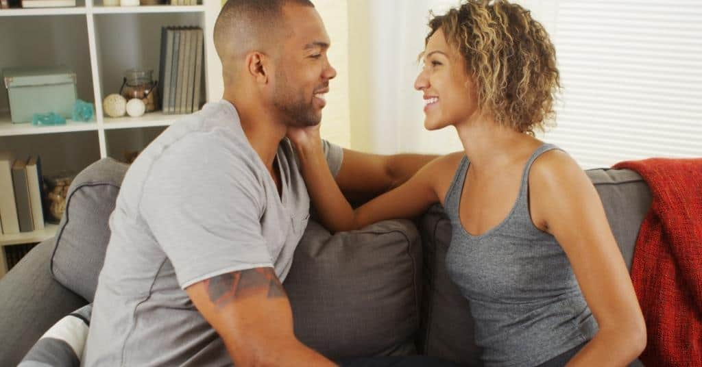 A couple looking at each other on the couch asking dirty would you rather questions for couples.