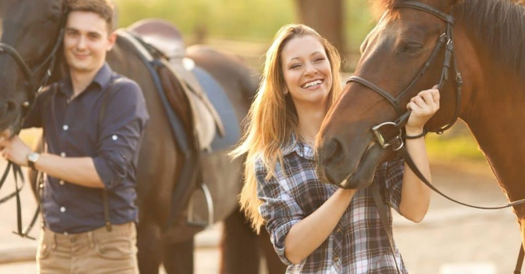 A couple standing next to their horses and smiling: a couples summer bucket list item.