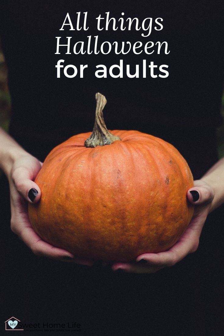 """A mid shot of a woman's hands with black nails holding a pumpkin and the text overlay, """"All things Halloween for adults."""""""