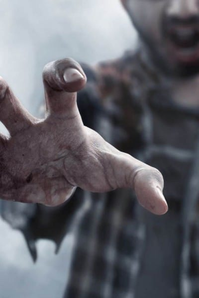 a zombie with his hand reaching towards the viewer