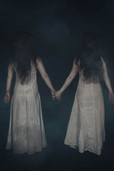 the back of two ghostly sisters who are walking hand in hand