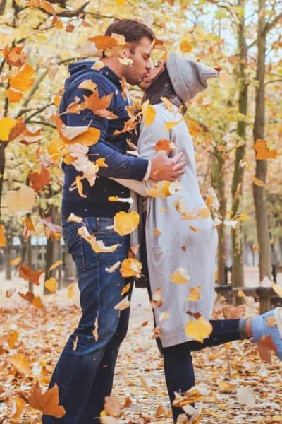 a couple kissing in the woods with leaves falling around them