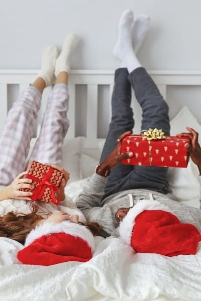 A couple lying on the bed with Santa hats om (and pajamas) holding gifts.