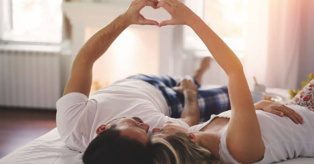 A couple lying on the bed making a love heart shape with their hands.