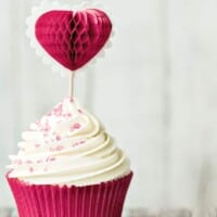 A Valentine's Day cupcake in a pink cpatty pan and a pink heart sticking from the top.