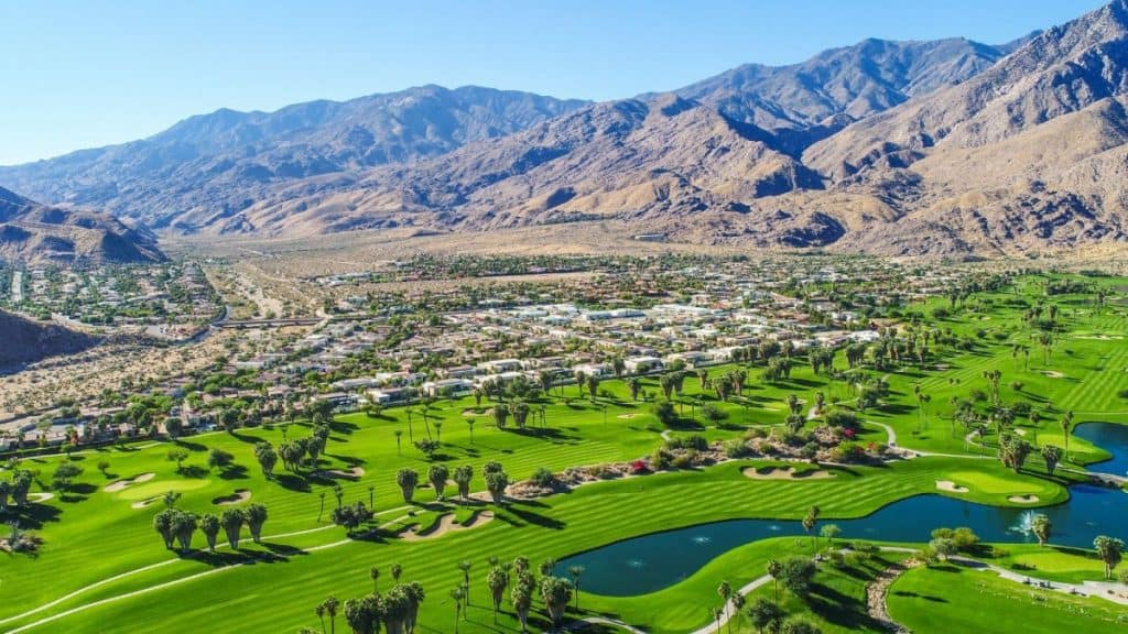 An aerial shot of Palm Springs showing lush green golf courses against the backdrop of the mountains: the scene for a fun weekend getaway from Los Angeles.