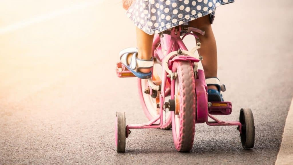 A young girl riding a bike with training wheels: one of the how well do you know me questions.