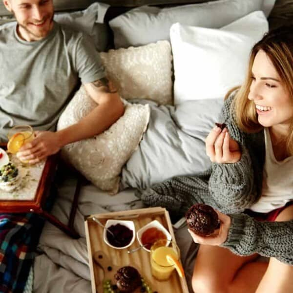 A couple enjoying breakfast in bed together - one of the fun things for couples to do at home