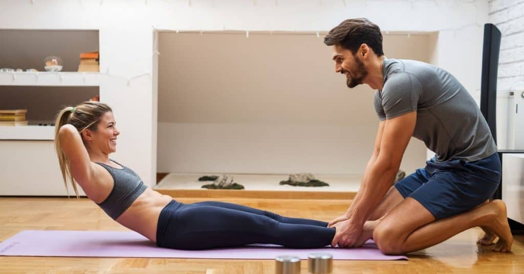 A couple doing a workout at home: one of the answers to what can couples do when bored at home?