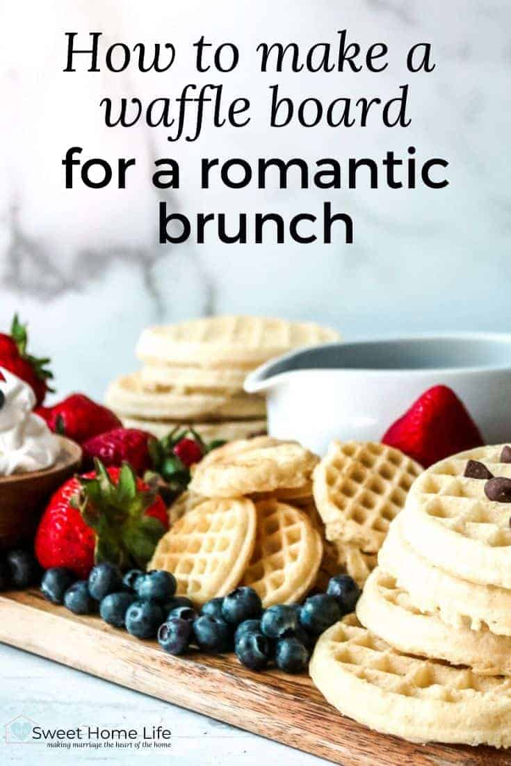 A waffle board featuring waffles, syrup, peanut butter, cream, blueberries and strawberries with the text overlay How to make a waffle board for a romantic brunch..