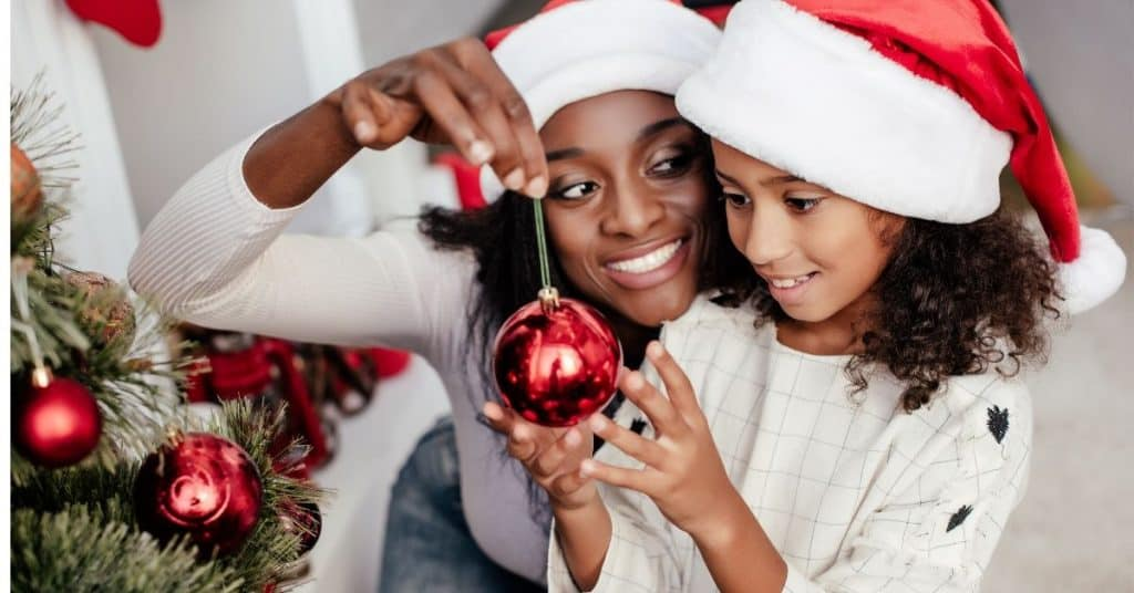 Woman handing her daughter an ornament to put on the tree.