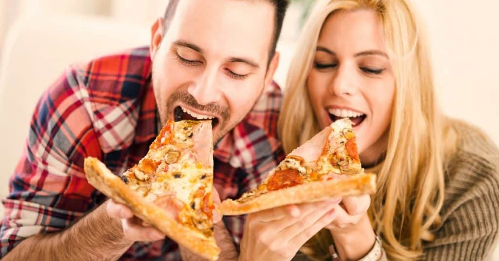 Couple eating a pizza together (challenging each other on who is most likely questions - to eat 2 pizzas in a sitting)