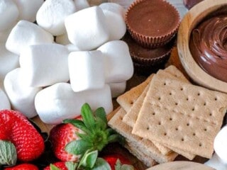 A smores board packed full of delicious ingredients including marshmallows, chocolates, peanut butter, crackers and strawberries.
