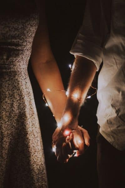 A couple holding hands with fairy lights entwined around them