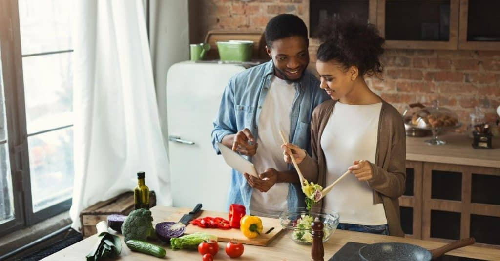 Woman making man dinner as one of the act of service ideas