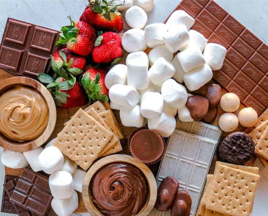 A smores board where you can see the chocolate placed around the board and the gaps filled in.