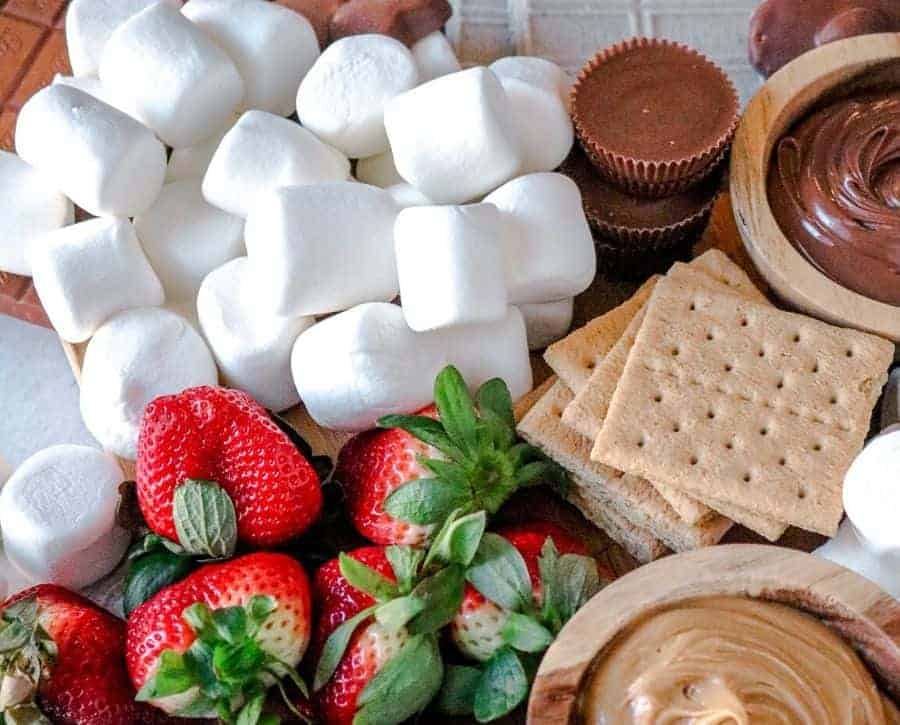 Gaps in the smores board filled with marshmallows and strawberries.