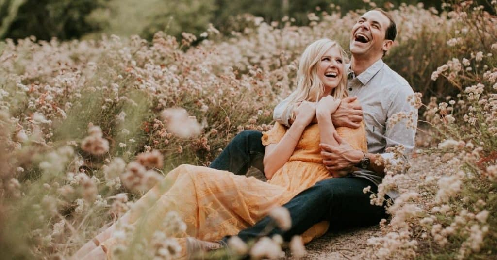 Couple sitting in a field. She is sitting between his legs and they are laughing.