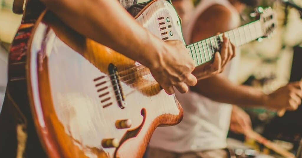Close up of a guitar being played in a concert