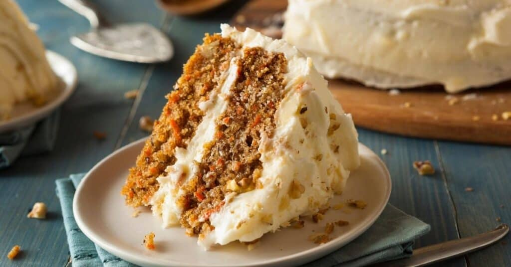 A slice of carrot cake on a plate next to a carrot cake.